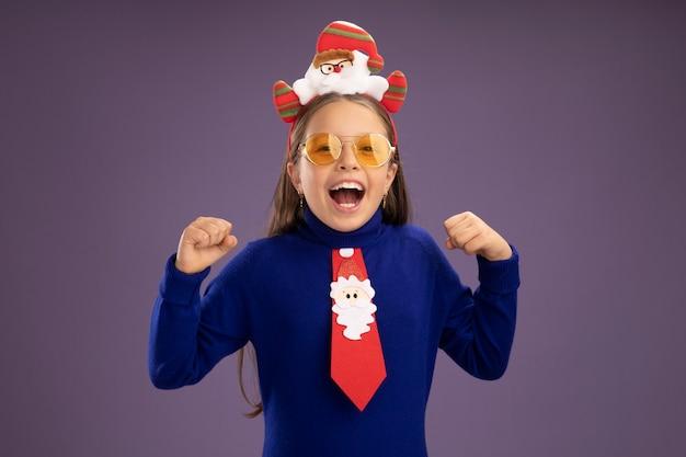 Klein meisje in blauwe coltrui met rode stropdas en grappige kerst rand op hoofd balde vuisten blij en opgewonden schreeuwen staande over paarse achtergrond