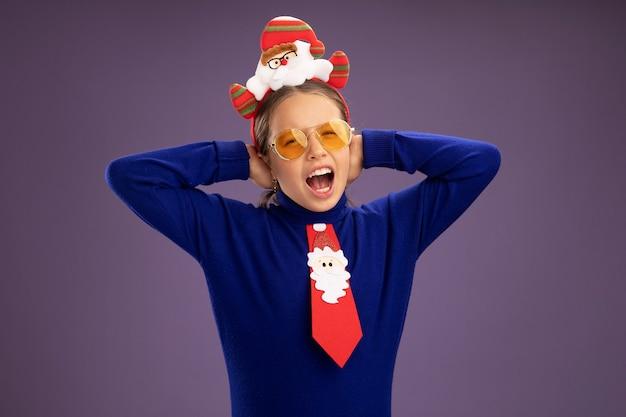 Klein meisje in blauwe coltrui met rode stropdas en grappige kerst rand op hoofd blij en opgewonden schreeuwen met opgeheven handen staande over paarse achtergrond