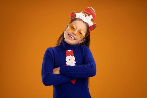 Klein meisje in blauwe coltrui met rode stropdas en grappige kerstrand op het hoofd lacht vrolijk met gekruiste armen over oranje muur