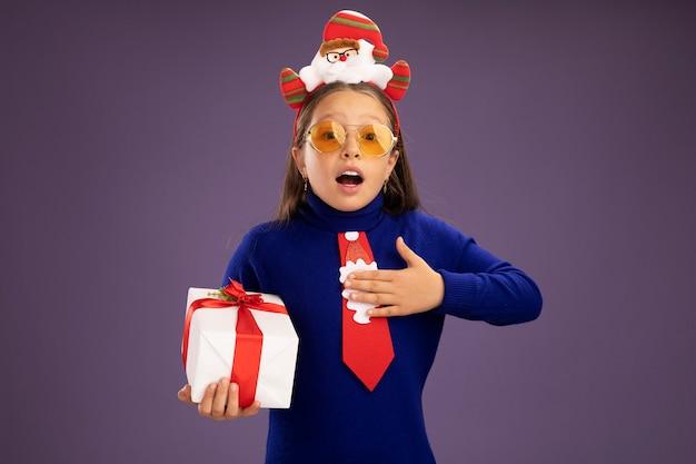 Klein meisje in blauwe coltrui met rode stropdas en grappige kerstrand op het hoofd met een cadeautje blij en positief met de hand op haar borst zich dankbaar voelend over de paarse muur