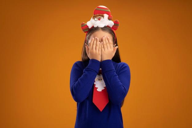 Klein meisje in blauwe coltrui met rode stropdas en grappige kerstrand op hoofd dat gezicht bedekt met armen die over oranje muur staan