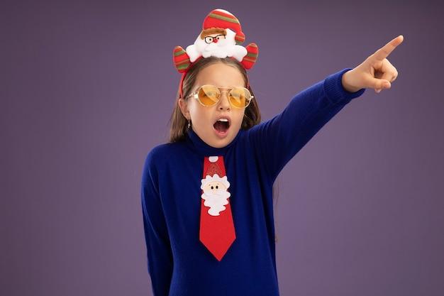 Klein meisje in blauwe coltrui met rode stropdas en grappige kerstrand op hoofd kijkend naar iets verbaasd wijzend met wijsvinger over paarse muur