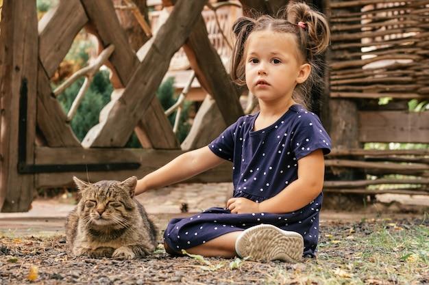Klein meisje in blauwe jurk zit op haar knieën in platteland en huisdierenkat, op de achtergrond van houten en rieten omheining
