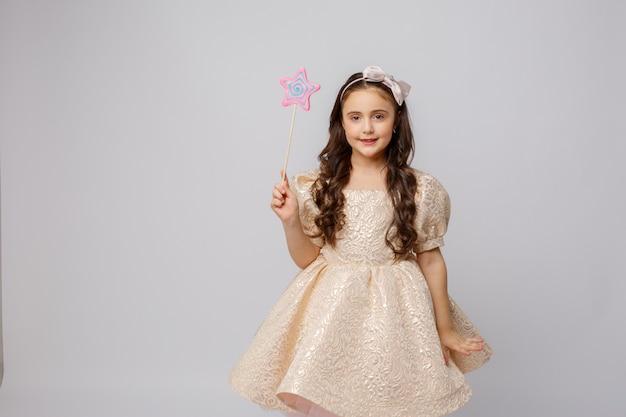 Klein meisje in de afbeelding van een fee met een toverstaf op een witte achtergrond
