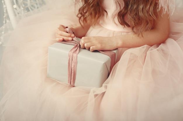 Klein meisje in de buurt van de kerstboom in een roze jurk