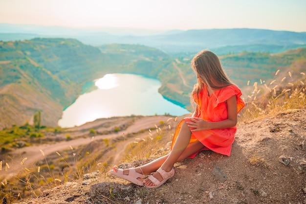 Klein meisje in de buurt van het meer overdag met geweldige natuur
