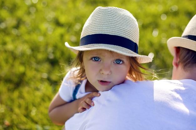 Klein meisje in de hooiberg in een hoed en een denim overall