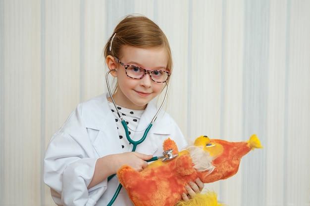 Klein meisje in de jas van een dokter glimlacht en nodigt uit om behandeld te worden. educatief medisch spel.