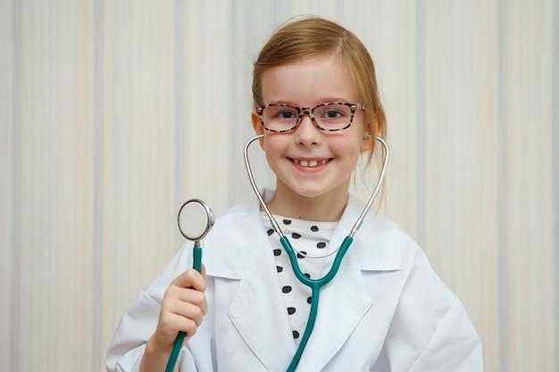 Klein meisje in de jas van een dokter glimlacht en nodigt uit om behandeld te worden.
