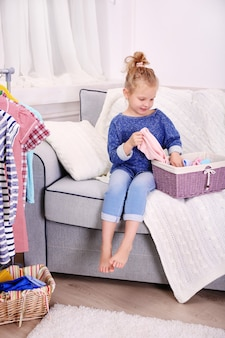 Klein meisje in de kamer met veel nieuwe kleren