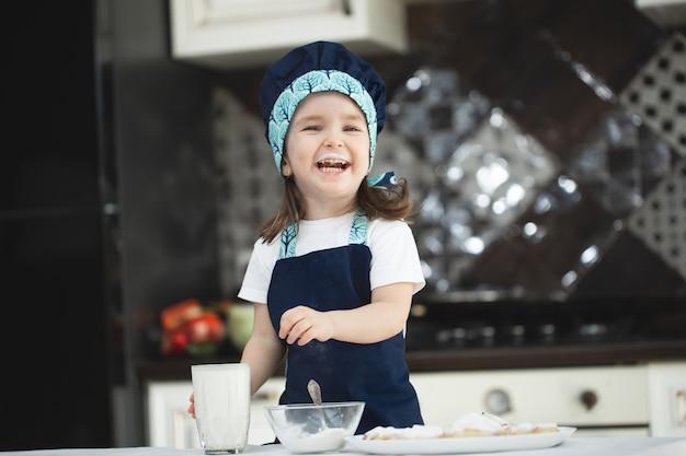 Klein meisje in de keuken in een schort en een koksmuts drinkt melk