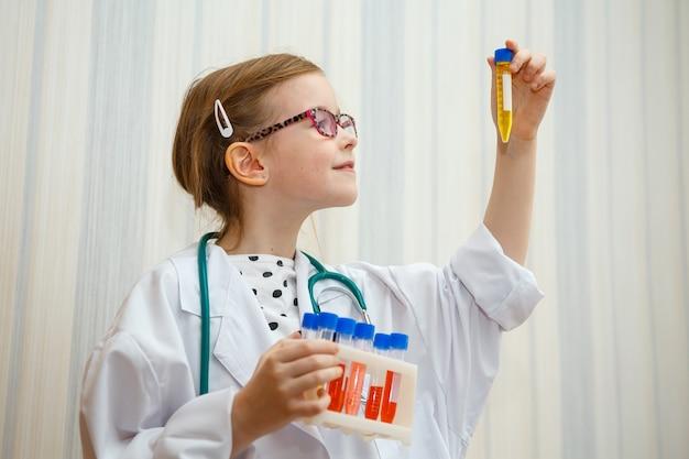 Klein meisje in de kiel van een arts onderzoekt reageerbuizen met tests. educatief medisch spel.