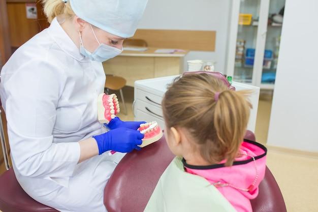 Klein meisje in de tandarts kliniek. gezondheidszorg, geneeskunde concept