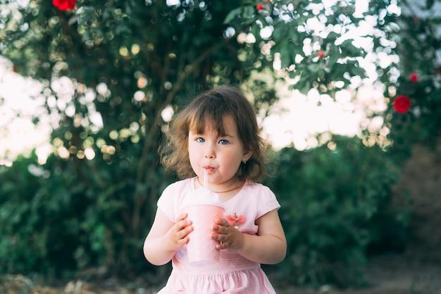 Klein meisje in de tuin met planten een drankje drinken uit een cocktail cup
