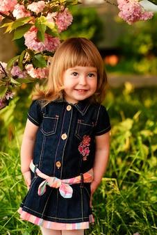 Klein meisje in de tuin, onder de sakuraboom. de lente