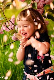 Klein meisje in de tuin, onder de sakuraboom. regen van lentebloemblaadjes.