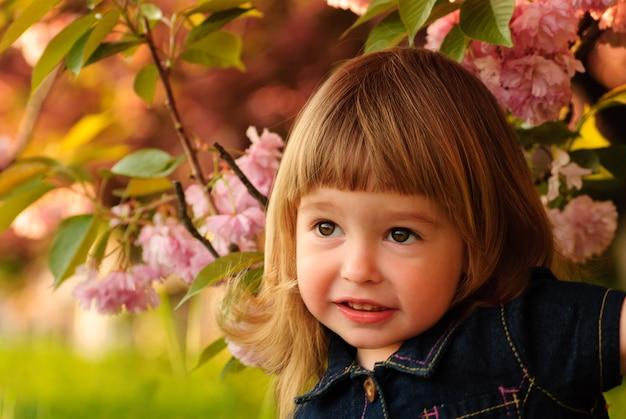 Klein meisje in de tuin onder de sakuraboom