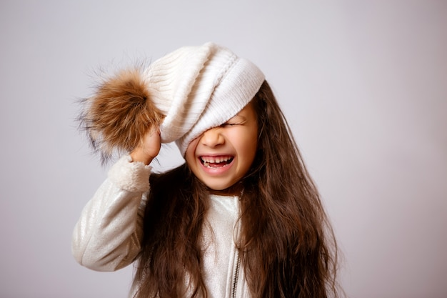 Klein meisje in de winter hoed lachend op wit