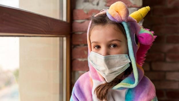 Klein meisje in dinosauruspak thuis met gezichtsmasker tijdens quarantaine
