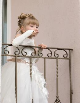 Klein meisje in een baljurk op het balkon