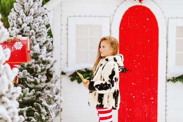 Klein meisje in een beige jas stuurt een brief naar de kerstman in een rode brievenbus
