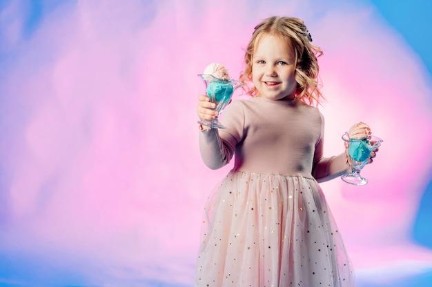 Klein meisje in een beige jurk houdt 2 ballen ijs in haar handen op een blauwe achtergrond en glimlacht