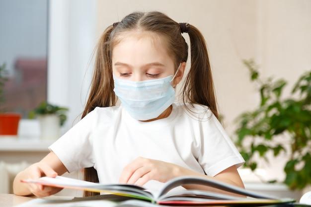 Klein meisje in een beschermend masker op afstand thuisonderwijs, quarantaine