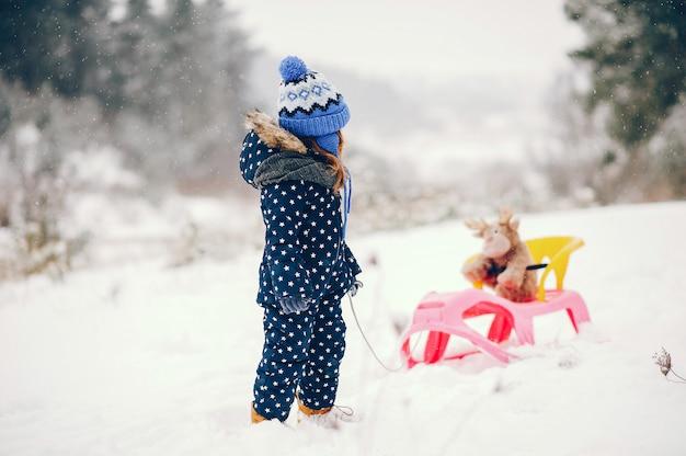 Klein meisje in een blauwe hoed die in een de winterbos speelt