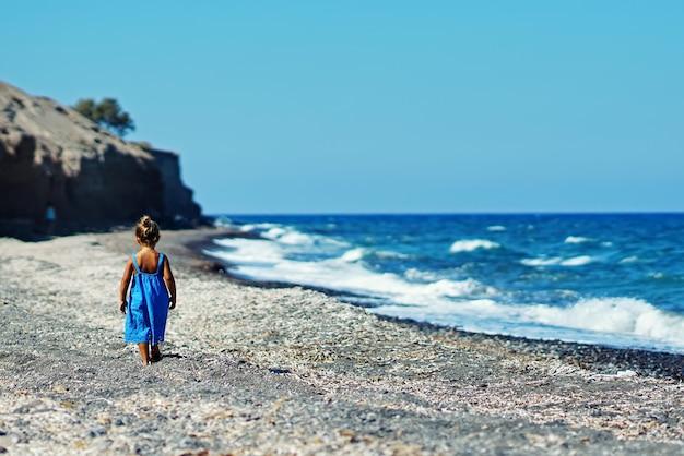 Klein meisje in een blauwe jurk spelen op het strand van paradisos in santorini