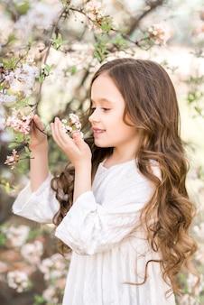 Klein meisje in een bloeiende lentetuin. het kind kijkt naar de witte bloemen.
