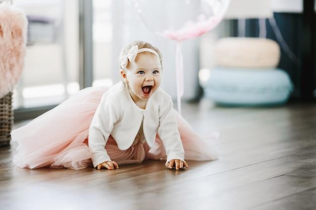 Klein meisje in een charmante roze jurk met open mond kruipt op de vloer