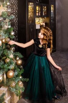 Klein meisje in een feestelijke jurk versieren de kerstboom, nieuwjaar concept. kid in de buurt van kerstboom, meisje in roze jurk.