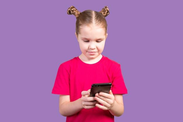 Klein meisje, in een fel t-shirt, gebruikt een smartphone geïsoleerd op een paarse achtergrond. voor elk doel.