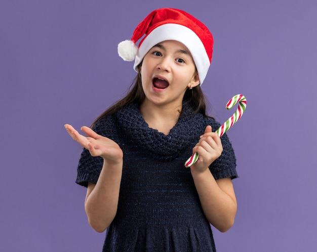 Klein meisje in een gebreide jurk met een kerstmuts en een snoeprietje, blij en verrast, staande over de paarse muur