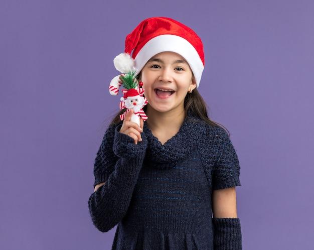 Klein meisje in een gebreide jurk met een kerstmuts met kerstsnoepgoed blij en vrolijk over de paarse muur