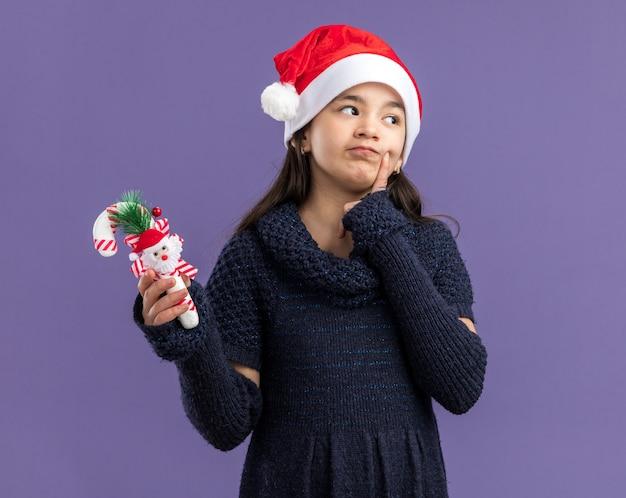 Klein meisje in een gebreide jurk met een kerstmuts met kerstsnoepgoed en kijkt verbaasd opzij terwijl ze over de paarse muur staat