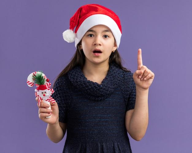 Klein meisje in een gebreide jurk met een kerstmuts met kerstsnoepgoed, verrast door de wijsvinger die over de paarse muur staat