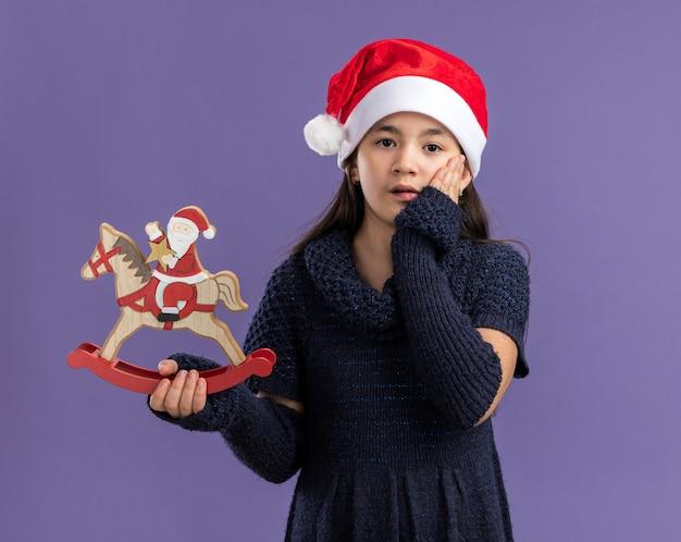 Klein meisje in een gebreide jurk met een kerstmuts met kerstspeelgoed verbaasd en verrast over de paarse muur