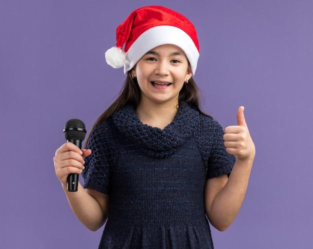 Klein meisje in een gebreide jurk met een kerstmuts met microfoon blij en positief met duimen omhoog staande over de paarse muur