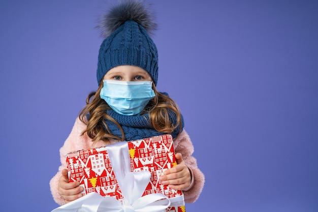 Klein meisje in een gebreide muts, sjaal en pluizige trui en een medisch gezichtsmasker met een kerstcadeau doos tegen paars.