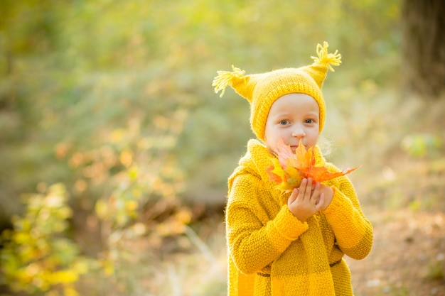 Klein meisje in een gele gebreide jas en hoed in herfst park.