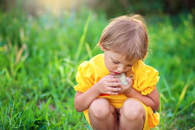 Klein meisje in een gele jurk zit in het gras en knuffelt zachtjes een kleine kip