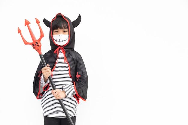 Klein meisje in een halloween-kostuum met een medisch masker halloween met veiligheidsmaatregelen van covid19