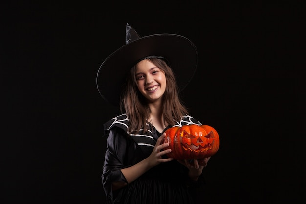 Klein meisje in een heksenkostuum dat hekserij doet op een enge pompoen. gelukkig kind in een heksenkostuum voor halloween.