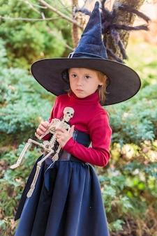 Klein meisje in een heksenkostuum met een skelet op een halloween-feest in de tuin