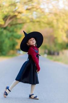 Klein meisje in een heksenkostuum staat op de weg op een halloween-feest in het dorp