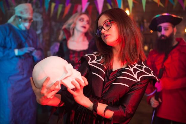 Klein meisje in een heksenkostuum voor halloween dat haar menselijke schedel vasthoudt en bewondert. griezelige heks.