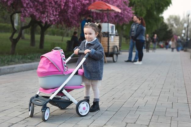 Klein meisje in een jas loopt in het park en rolt een speelgoedbuggy met een pop