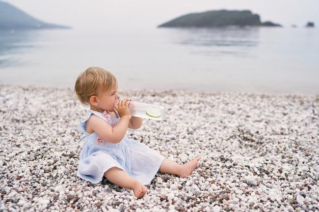 Klein meisje in een jurk drinkt water uit een fles op een kiezelstrand