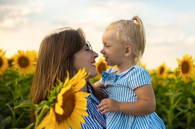 Klein meisje in een jurk en bril kijkt naar haar moeder op een zonnebloemveld. vriendelijke familie.